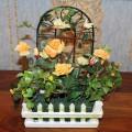 Искуственные желтые розы в заборе